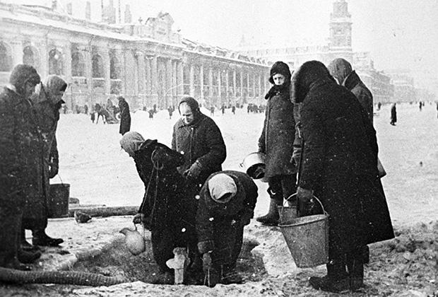 Жители блокадного Ленинграда набирают воду, появившуюся после артобстрела в пробоинах в асфальте на Невском проспекте. Декабрь 1942 г.