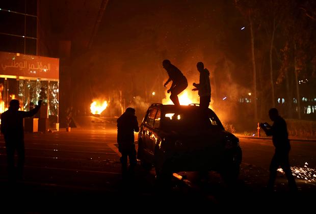 Демонстранты на фоне огня взбираются на автомобиль, припаркованный у здания Национального конференц-зала. Протестующие и вооруженные мятежники заставили временное правительство спешно покинуть это место.