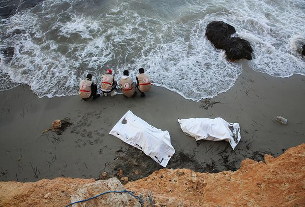 Сотрудники Международного движения Красного Креста и Красного Полумесяца омывают руки после того, как уложили тела погибших мигрантов в мешки.