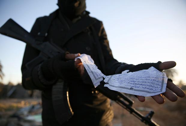 Сотрудник правительственных сил Ливии демонстрирует бумажку, на которой на арабском языке описывается вооружение. Документ был найден на месте, по которому был нанесен авиаудар США в рамках уничтожения лагеря боевиков запрещенного на территории России «Исламского государства». В результате погибли десятки людей.