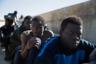 Мигранты отдыхают на тротуаре в порту. Они были спасены береговой охраной у побережья Триполи.