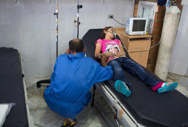 Сириец склоняется над больничной койкой, на которой лежит его дочь. Он, как и тысячи других мигрантов, оказался на лодке, перевернувшейся у побережья города Зувар. Сколько людей утонуло в результате этого инцидента, неизвестно.