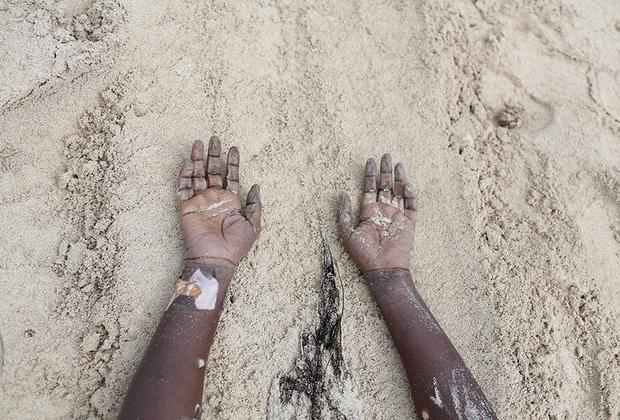 Руки африканской женщины, тело которой вымыло на побережье Зувары. Она, как и тысячи других мигрантов, отправилась на лодке в сторону Европы за лучшей жизнью и погибла, так и не доплыв до цели. Согласно данным Международной организации по миграции, только в 2014 году в Средиземном море утонули более 1,8 тысячи мигрантов.
