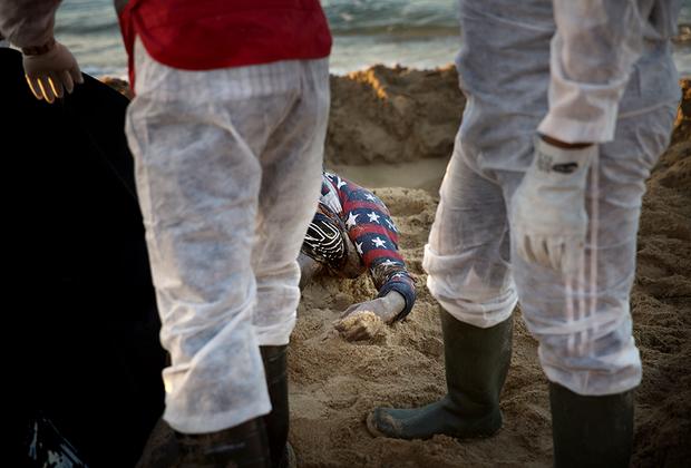 Сотрудники ливийского отделения Международного движения Красного Креста и Красного Полумесяца вытаскивают из песка безжизненное тело утонувшего мигранта. В течение нескольких дней после того, как у восточного побережья Триполи затонула лодка с мигрантами, волонтеры обнаружили 11 тел.