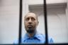 Саади Каддафи, сын свергнутого лидера Муаммара Каддафи, за решеткой в зале суда. Ему предъявлено обвинение в причастности к убийству футболиста Башира Аль-Рияни. Только в 2018 году суд Триполи постановил признать его невиновным в убийстве, обмане, угрозах, порабощении и диффамации Рияни.