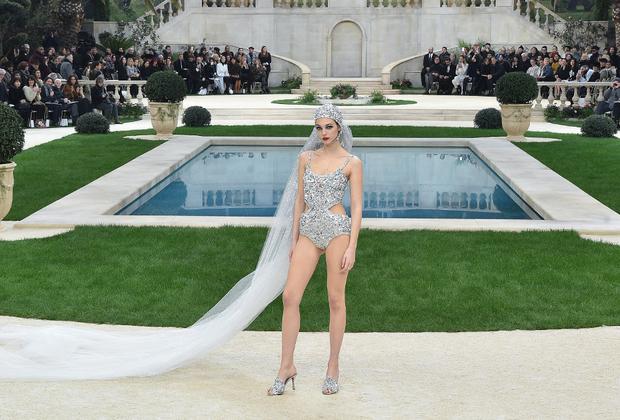 """Главной сенсацией показа Chanel стало отсутствие на финальном поклоне главы дома Карла Лагерфельда. Встревоженным поклонникам сообщили, что мэтр просто <a href=""""https://lenta.ru/news/2019/01/22/tiredfeld/"""" target=""""_blank"""">устал</a>. Было от чего: как всегда, шоу проходило с невероятным размахом. На сей раз под стеклянной крышей Гран-Пале соорудили роскошную виллу с бассейном в стиле Людовика XIV. Модель Виттория Черетти вышла на дорожку-подиум в фате, головной повязке в духе 1930-х годов и серебристом купальнике."""