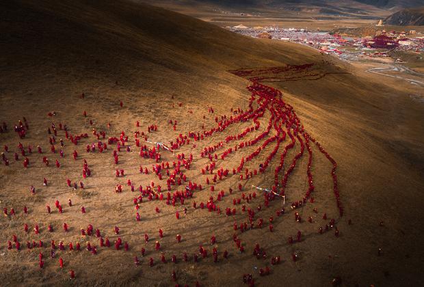 «Красная река веры» Лифеня Чена. Тысячи буддистских женщин выстроились в линии на пути в горы, где они займутся практикой Дхармы Да Юань Шень Хуй. Провинция Сычуань, Китай.