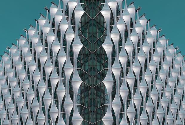 «Новое посольство США в Лондоне было разработано бюро Кирана Тимберлейка и построено компанией Nine Elms на берегу Темзы. По сути, это стеклянный куб, окутанный мерцающими парусами из пластика. По словам архитекторов, «прозрачный кристаллический куб» призван символизировать «прозрачность, открытость и равенство». Необычная форма фасада здания спроектирована таким образом, чтобы минимизировать солнечные блики, в то же время пропуская естественный свет в офисные помещения.   Светоотражающий фасад меняет цвет в зависимости от погоды и положения солнца. «Я нахожу это здание совершенно очаровательным, простым, но привлекательным. Мое намерение состояло в том, чтобы создать изображение, которое заключает в себе его красоту и уникальную форму», — рассказывает фотограф из ЮАР Катаржина Янг.