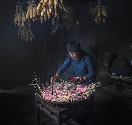 «Рисуя счастье» авторства Мин Кай Чан. Снимок сделан в удаленной деревне в западной части провинции Хунань в Китае, где проживает этническое меньшинство. Осенью люди делают заготовки еды на зиму. Деревенская женщина рисует традиционные символы на сухом рисовом пироге в надежде на счастливый и здоровый год.