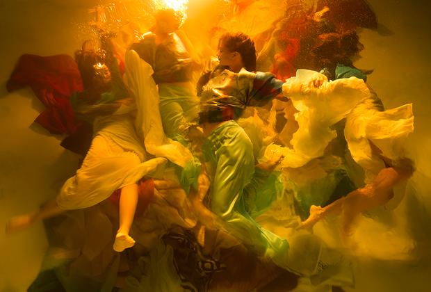 """«Фотография """"Гармония"""" посвящена красоте и уязвимости человеческой жизни. Снимок сделан под водой на Гавайских островах. Это часть большой коллекции под названием """"Музы"""". Цвета, каскад тел, контраст света и тени использованы, чтобы создать ощущение движения в кадре. Мое положение снаружи бассейна сделало поверхность воды своеобразным холстом, а также дало возможность показать такие красивые природные эффекты, как преломление света и мягкие пузыри», — комментирует свой снимок американка Кристи Ли Роджерс."""