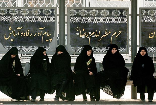 Женщины ждут автобус на остановке в Мешхеде —втором по размерам городе Ирана, который считается религиозной столицей страны. Многие современные иранки закрывают все, кроме лица, и носят исключительно одежду черного цвета. Фотография сделана в 2008 году.
