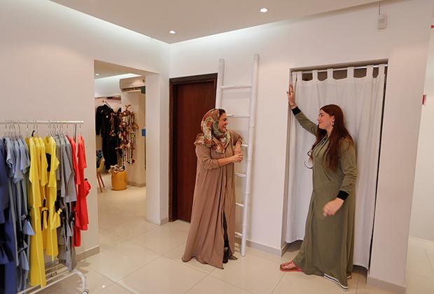 Некоторые саудовские женщины постепенно отказываются от total-black. Но одеться по-европейски для жительниц королевства по-прежнему невозможно. На фото: дизайнер Иман Джохари и одна из ее клиенток в бутике в Джидде.