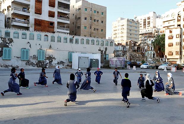 Группа девушек разминается перед забегом в Джидде. Если в зале саудовские женщины еще могут распустить волосы, то при занятиях на открытом воздухе обязаны соблюдать религиозные правила.