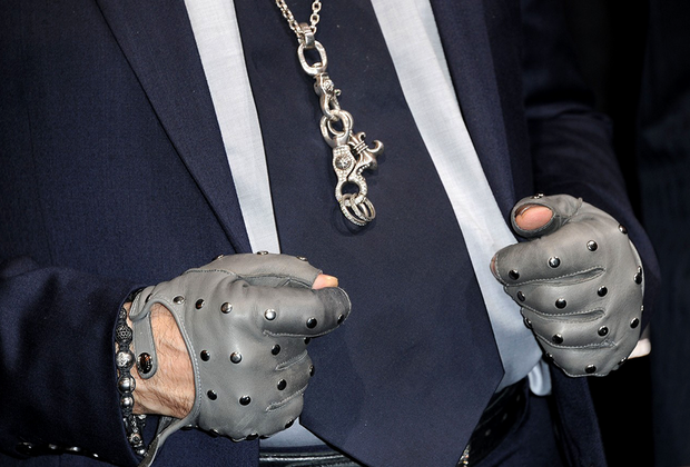 Модельер всегда был поклонником броских аксессуаров: помимо черных очков, он носил массивные цепи, браслеты и перчатки автогонщика.
