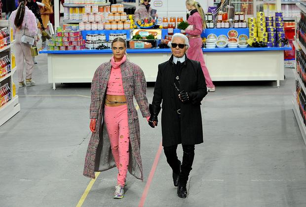 В финале показа, декорации которого были стилизованы под гигантский супермаркет, Лагерфельд вышел на поклон с одной из своих фавориток 2010-х — моделью Карой Делевинь.