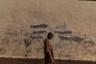 Мальчик-сирота у стены, на которой изображена атака противотанковых гранатометов в городе Бол в Чаде. Номинация «Окружающая среда».
