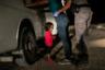 Американские пограничники обыскивают мать Янелы, вместе с дочкой она прибыла из Гондураса. Янела с матерью стали частью «каравана мигрантов», который пытался пробраться в США по реке Рио-Гранде. Девочке тогда не было и двух лет.  <br> <br> По распоряжению властей нелегальных мигрантов разлучали с детьми. Хоть Янела с матерью не были разлучены, считается, что этот снимок изменил положение вещей. Вскоре после его публикации президент США Дональд Трамп прекратил практику разделения семей.