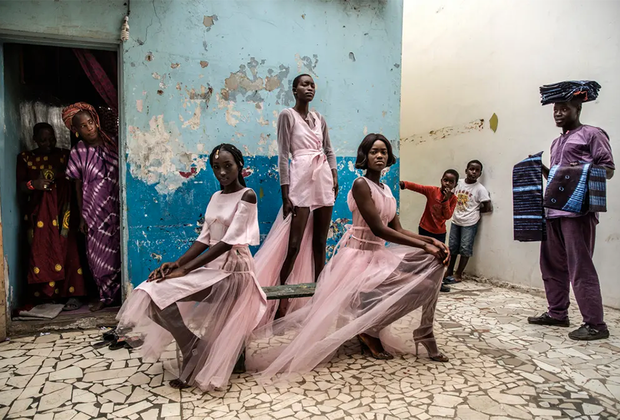 Любопытные жители и уличный торговец наблюдают за тем, как три модели на улице Дакара позируют в нарядах сенегальского дизайнера. Номинация «Одиночные портреты».