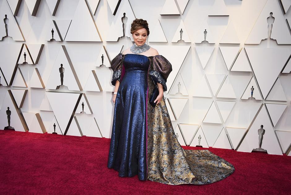 Рут Картер, художница по костюмам фильма «Черная Пантера», самостоятельно выбрала для себя платье из синей парчи в стиле ампир, с пышным аристократическим шлейфом.