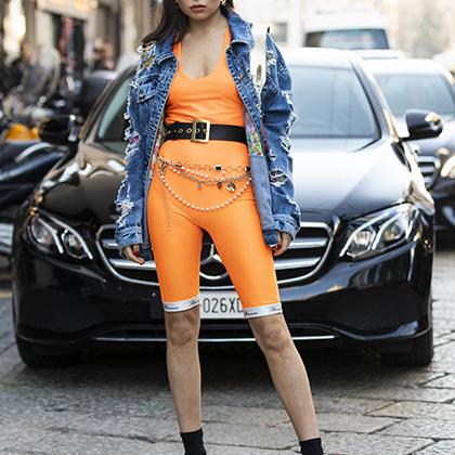 Поклонница бренда, невзирая на довольно прохладный миланский февраль, надела на показ вырвиглазно-оранжевые велосипедки Blumarinе с топом в тон, широким ремнем и драной джинсовой курткой. Выглядит так, словно девушка сбежала с рейва середины 1990-х.