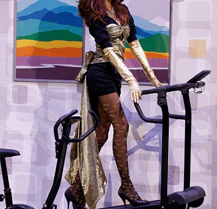 Еще одна аллюзия к 1980-м от Джереми Скотта: модель с пышным начесом демонстрирует мини-шорты, принтованные колготки и парчовый топ, шагая на шпильках по спортивному тренажеру.