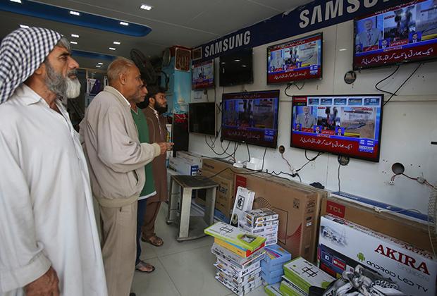 Пакистанцы смотрят новости в городе Карачи