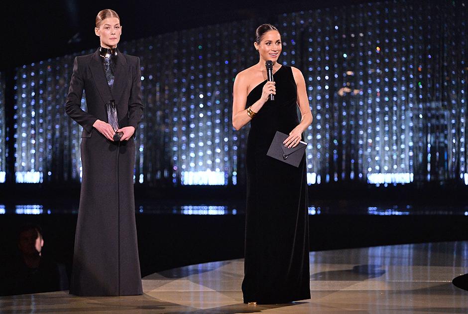 На сцену королевского Альберт-холла герцогиня Сассекская поднялась в платье Givenchy. Выбор бренда был неслучаен: Меган вручила премию The Fashion Awards 2018 креативному директору бренда Клэр Уэйт Келлер, которая сшила для нее свадебное платье. Асимметричный наряд с одним открытым плечом (за его чрезмерную откровенность, неуместную для особы из королевской семьи, Меган не раз упрекали в прессе и соцсетях) герцогиня дополнила туфлями Tamara Mellon и браслетами одной из своих любимых марок — Pippa Small.