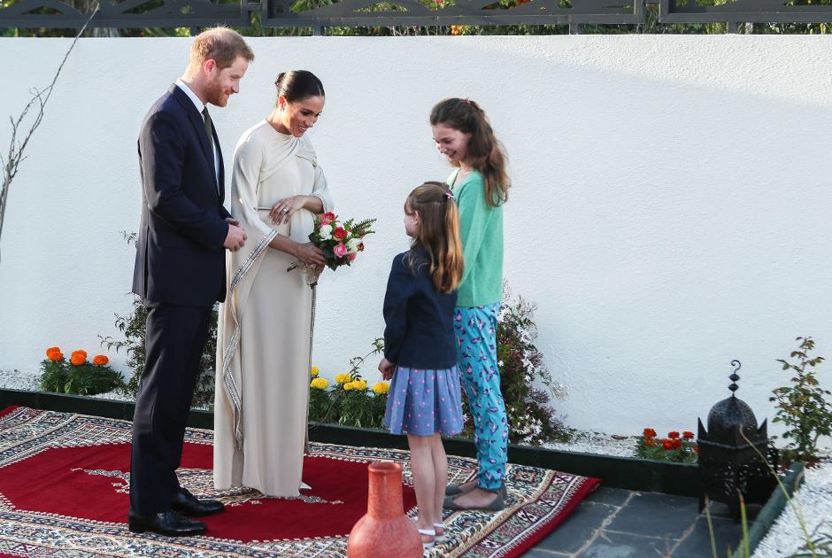 Для приема в британском посольстве в столице Марокко Рабате Меган выбрала еще более формально скромное (хотя по сути роскошное) и официальное платье Dior сдержанного оттенка морского песка. Рядом с встречающими ее девочками в неформальной домашней одежде (вероятно, дочерями посла) герцогиня выглядит вопиюще overdressed.