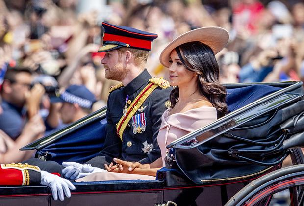 На параде Trooping of the Colour Меган восседала в коляске в пепельно-розовом платье Carolina Herrera с вырезом лодочкой, открывающем верх плеч. Консерваторы шипели, что она скандализирует публику, а прогрессивная публика заявила, что герцогиня приучает двор к своему собственному стилю. Шляпка в тон платью от дизайнера Филипа Трейси ни у кого возражений не вызвала: его услугами пользуются и другие дамы королевской семьи.