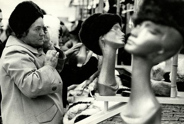 Позирующим моделям он предпочитал обыкновенных прохожих и их естественные эмоции, поэтому старался фотографировать незаметно, как эту женщину, старательно выбирающую шляпку.