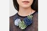 Многие современные женщины следуют заветам Коко Шанель и носят броскую модную бижутерию вместо классических бриллиантов. Хороший подарок для таких девушек — колье со стилизованными цветами из полосок экокожи.