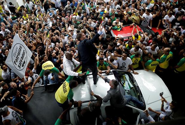 Марселино также освещал президентскую предвыборную гонку в Бразилии, в которой одержал победу одиозный политик Жаир Болсонару. Он известен крайне правыми взглядами, скандальными и оскорбительными высказываниями.  В 2017 году его приговорили к штрафу за то, что во время перебранки с депутатом Марией до Розарио (которая назвала его насильником) он заявил, что «она даже не достойна быть изнасилованной им». <br> <br> Болсонару— сторонник военной диктатуры и выступает за смертную казнь. На фото он в окружении сторонников за несколько месяцев до избрания президентом страны.