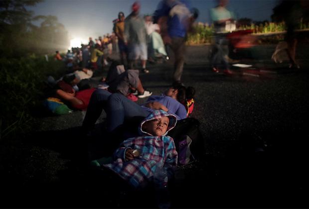 В начале пути численность каравана составляла около пяти тысяч человек. До самого западного города Мексики Тихуаны, по разным оценкам, дошли от 7 до 10 тысяч человек. Они прорвались через пограничные посты и возвели у границы США палаточный городок под открытым небом.  <br> <br> На фото — 33-летняя Гленда Эскобар с малолетним сыном. Они проделали путь в сотни километров из Гондураса и остановились на ночевку в мексиканском городе Пихихьяпан.