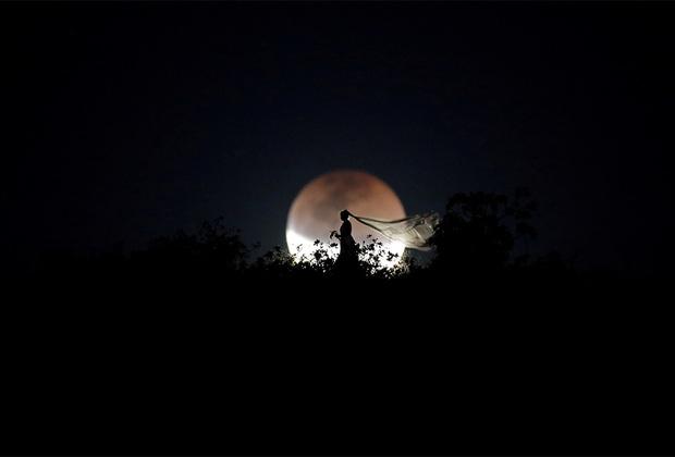 Тема мигрантов — не единственное, что интересовало Уэсли Марселино в минувшем году. Фотограф следил за полным лунным затмением, которое наблюдалось в Южном полушарии 27 июля. На фото — бразильская невеста позирует на фоне Луны во время астрономического явления.