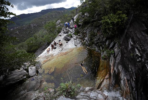 Посетители бразильского Национального парка Chapada dos Veadeiros купаются в водопаде.