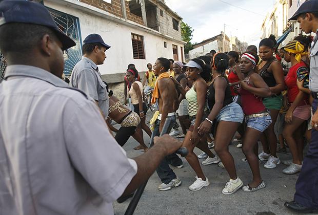 Тысячи молодых людей танцуют под ритмы конга на улицах Сантьяго-де-Куба в честь очередного юбилея Кубинской революции.