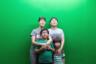 Корейская семья фотографируется на память в пусанском океанариуме. Зеленый экран поменяют на рыб и морскую живность в фоторедакторе.