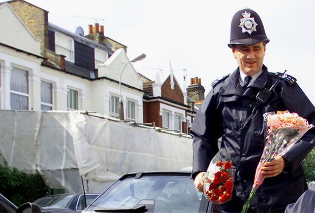 Сотрудники полиции возлагают цветы на месте убийства любимицы Британии