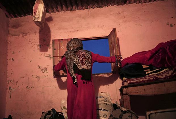 Умм Яссер закрывает окно в своем доме. Бедуинские деревни, расположенные в глубине Синайского полуострова, остались вдали от туристических маршрутов и курортов побережья. Их жители страдают от безработицы и живут в нищете.