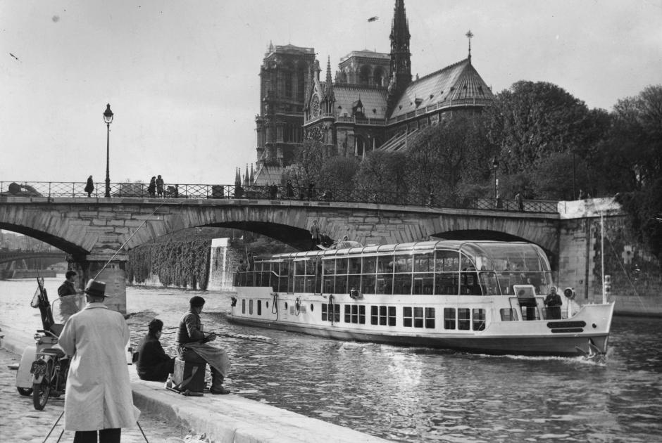 В 1954 году, когда был сделан этот снимок, Нотр-Дам де Пари, как и в наши дни, был обязательной для посещения достопримечательностью, к которой стремилось множество туристов. Они огибали остров Сите в речном трамвайчике, идущем по Сене, фотографировали его с набережной и просто любовались древним собором.