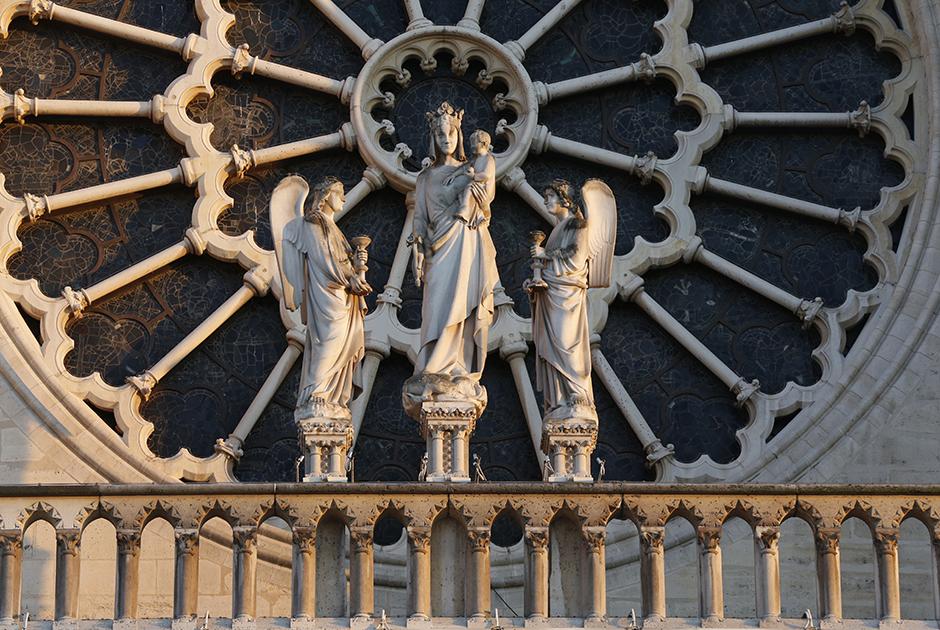 С внешней стороны центральную розу украшала статуя Богоматери в венце, с младенцем-Христом на руках и двумя предстоящими ангелами.