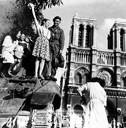 Молодая парижанка празднует освобождение города на броне британского танка напротив Нотр-Дам де Пари.