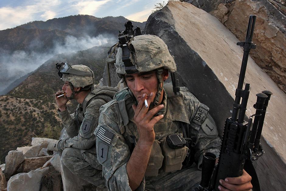 Мур побывал на самой продолжительной в истории США войне в Афганистане. Государство ввело туда войска в ответ на теракты 11 сентября 2001 года. Одновременно США вели две антитеррористические войны. Во вторую —  в Ираке —  Штаты ввязались в 2003 году. В Афганистане погибло около 2,5 тысячи американских военнослужащих. 2008 год, когда был сделан этот снимок, стал годом укрепления Талибана в регионе. Уставшее от войны население испытывало недовольство присутствием НАТО и склонялось на сторону талибов, которые усилили информационную войну.  <br> <br> На фото: пехотинцы Джеймс Хоррис (James Horris) и Кевин Йетман (Kevin Yeatman) присели покурить после перестрелки с талибами. Они начали палить по американцам, когда их полк занял стратегическую вершину. Никто из американских военных в той перестрелке не пострадал.