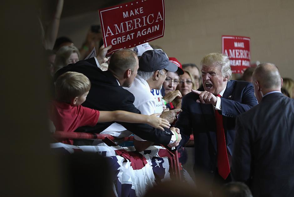 Дональд Трамп во время президентской кампании, окруженный своими сторонниками в штате Пенсильвания. Кандидат, обещающий «сделать Америку великой снова», только что выступил перед пятью тысячами жителей городка Механиксбург. Пенсильвания стала последним штатом «ржавого пояса»— промышленных регионов, который посетил Трамп. Этот штат принадлежал к числу колеблющихся, однако в ноябре 2016-го все-таки проголосовал за Трампа.