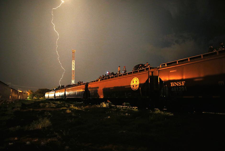 Фото сделано задолго до нашествия каравана беженцев, в августе 2013 года. Мексиканцы всегда всеми правдами и неправдами стремились в соседнюю Америку, которая сулила высокие в сравнении с местными заработки. Некоторые добирались до США на крышах поездов. Это один из самых опасных нелегальных способов попасть в Штаты. Мигранты теряют конечности и погибают под колесами поездов, остальных грабят местные банды.