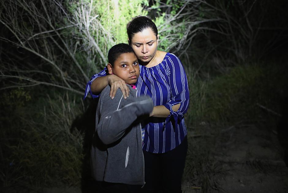 Испуганных мать и сына из Гондураса задержали вблизи границы США с Мексикой. Они переплыли реку Рио-Гранде и заблудились в лесу, где 12 июня 2018 года были пойманы и отправлены в центр временного содержания, где их, возможно, разлучат.