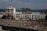 Йемен и до начала конфликта считался одной из беднейших стран арабского мира. Насилие, голод и болезни истощили и без того захиревшее государство. Города, за которые развернулась наиболее ожесточенная борьба, превратили в призраки. О том, что в этом здании в Адене раньше располагался офис Mercedes-Benz, напоминает лишь побитая вывеска. На момент съемки в бывшем представительстве немецкой компании укрывались люди. Они заколотили окна досками, чтобы защититься от обстрелов.