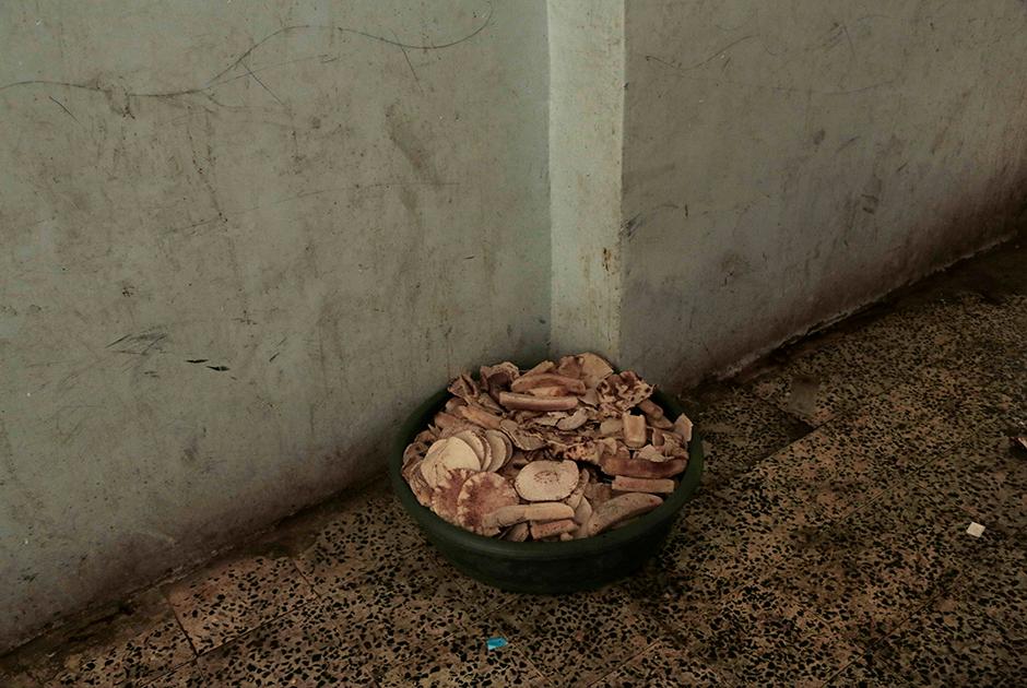 Ведро с хлебом в йеменском приюте для беженцев. Расследование Associated Press показало, что несмотря на большие объемы поступаемой в страну гуманитарной помощи, пища часто не доходит до тех, кто в ней больше всего нуждается. Завладевшие едой группировки перенаправляют ее в свои боевые подразделения или продают на черном рынке.