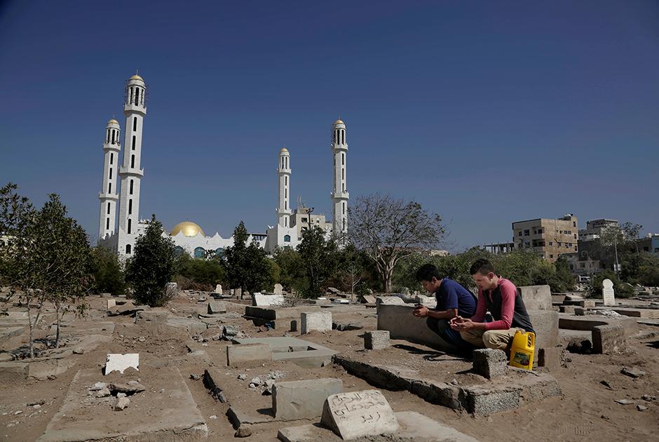 Два местных жителя — Осама Ахмед и Ахмед Салех — молятся у могил товарищей, погибших в битве за Аден в 2015 году.