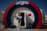 Гид проекта C-Space позирует на входе в шлюзовую камеру марсианской станции, одетая в скафандр, который гипотетически может использоваться в китайской марсианской программе.